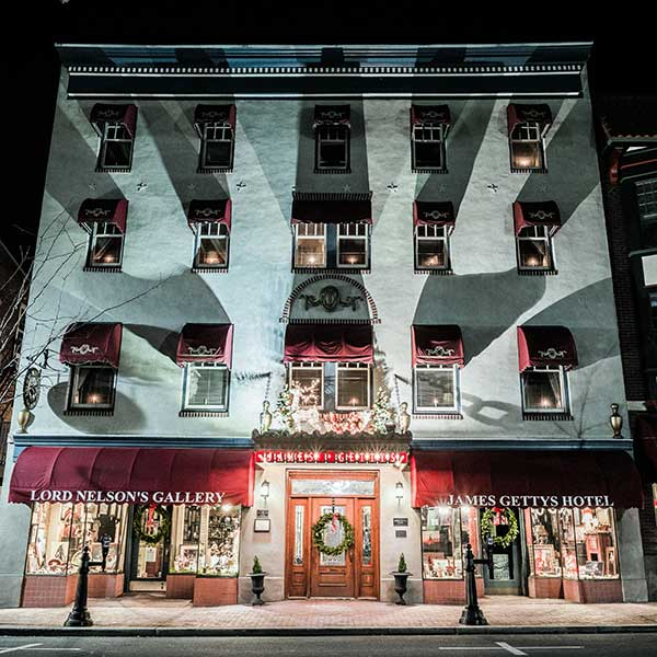 A dramatic exterior of the Gettysburg hotel, at night, the windows are illuminated by dramatic spotlights, casting a radial pattern that draws your attention to the front door, where some guests enter, but never leave.