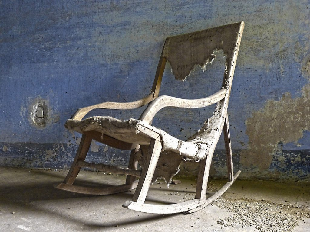 an old rocking chair with peeling paint