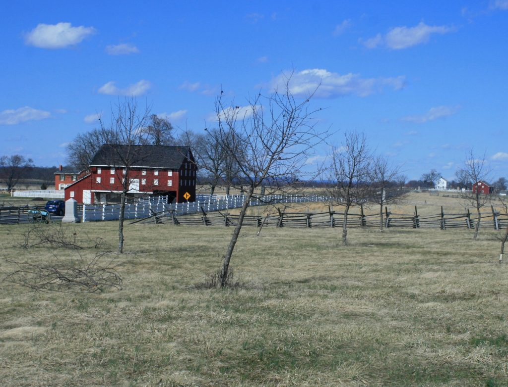 photo shows a red barn in the distance, past a peach orchard.