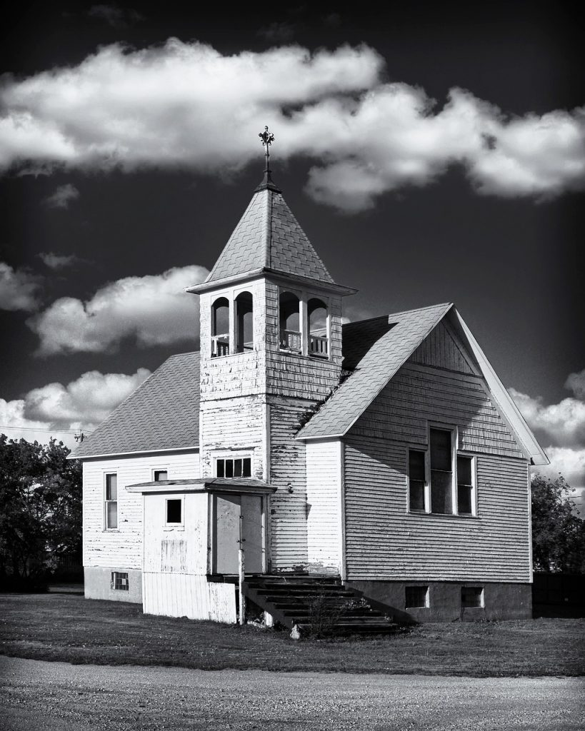 Picture shows a small white church in black and white.