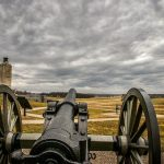 photo shows a cannon pointing towards the gettysburg battlefield under cloudy skies