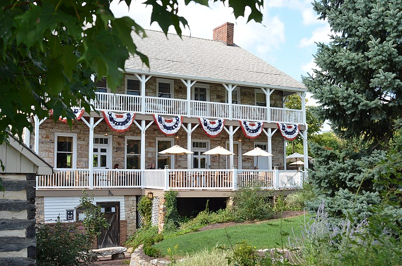 photo shows the facade of the Jean Bonnet Tavern, with american flags hanging from a double deck front porch