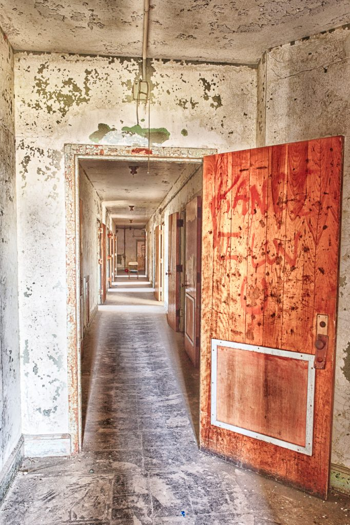 photo shows a rusted red door leading into an abandoned hospital hallway