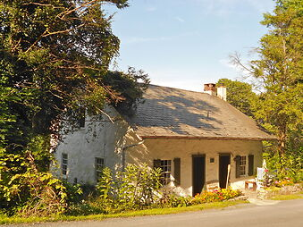 photo shows the front of the Schaumboch Tavern, a small stucco building off the side of a road.