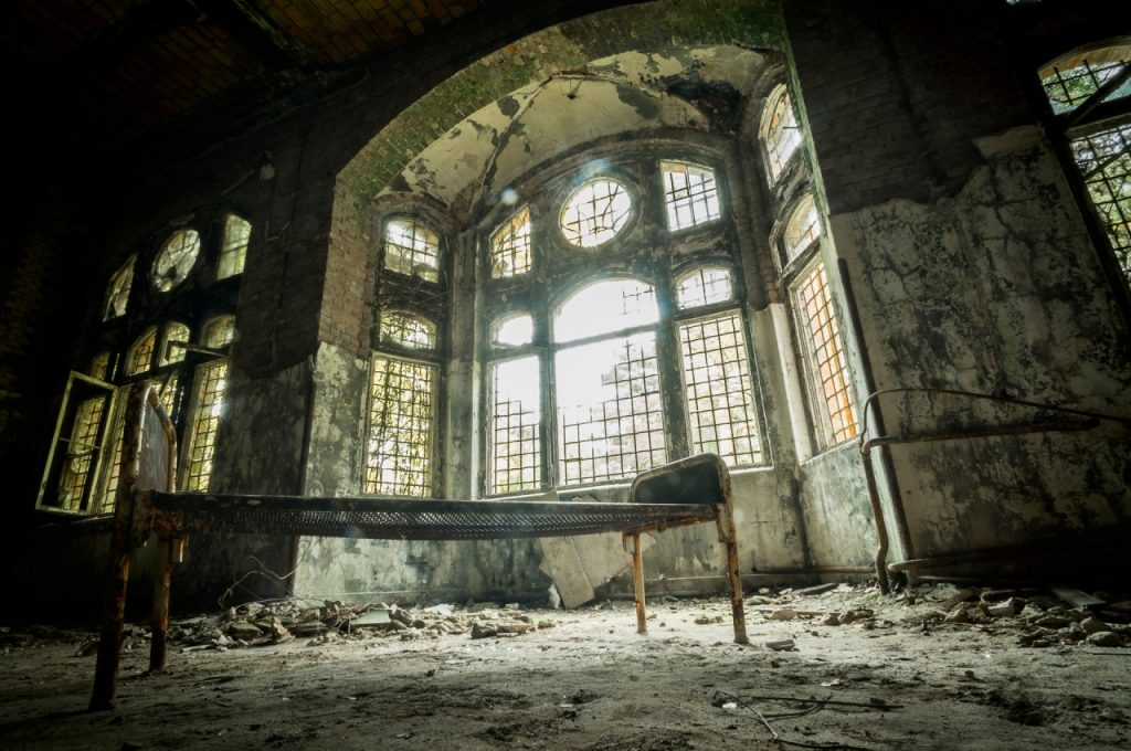 photo shows a large window covered with vines, dust, and shadows. It is obviously abandoned