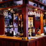 photo shows a bar counter with glasses hanging and lots of beer selection