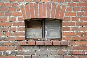 photo shows a brick wall with an old window