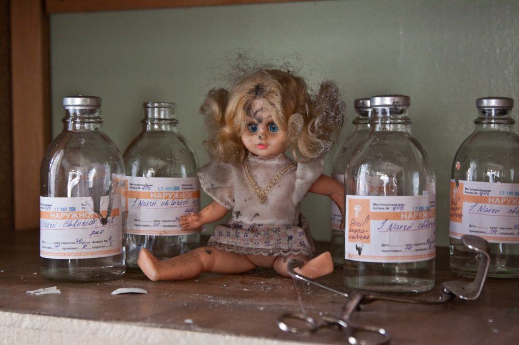 photo shows a creepy doll sitting next to some old vaccine bottles