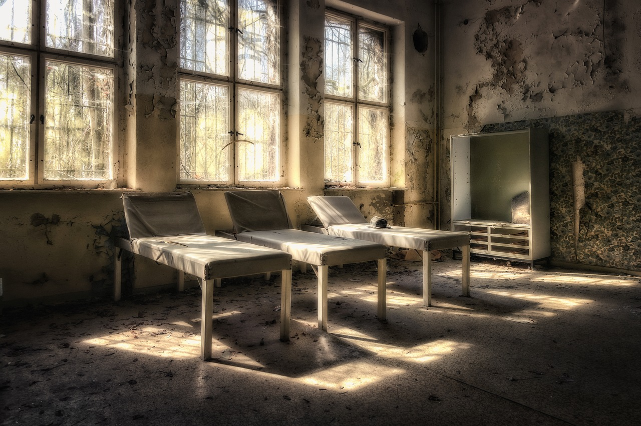 photo shows three abandoned hospital beds bathed bu golden sunlight in a dark room.