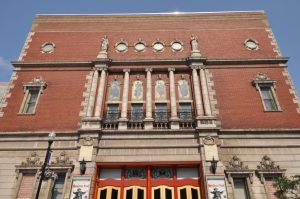 photo shows a front view of the mishear theatre with its bright red doors