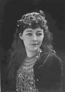 photo is a black and white portrait of singer May Yohe, with jewels on her head and neck.