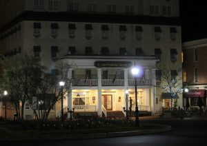 Photo shows the façade of the Gettysburg Hotel at nighttime, with only a small streetlamp illuminating the outside.