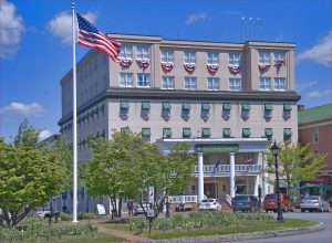 Photo shows the façade of The Gettysburg Hotel with an American flag on a flagpole and numerous other American flags hanging from the windows of the upper story. The building is made of grey brick with small green awnings over the windows.